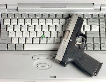 Photograph of a pistol on a computer laptop keyboard
