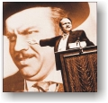 Photograph of Charles Foster Kane pointing to poster of himself.